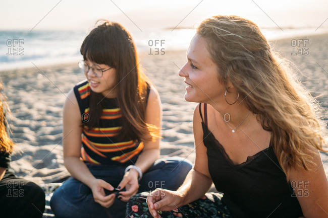 A beautiful blonde girl chatting with her group of friends on the beach, next to her Asian friend