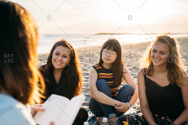Three beautiful women paying attention to their friend who reads them a book on the beach, blonde girl, brown hair girl and Asian girl with the sun behind her Concept of vacation