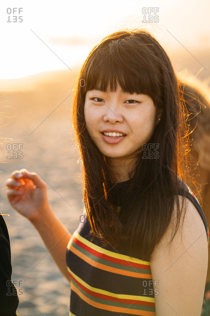 Colorful portrait of a beautiful Asian girl on the beach with the sun shining on her hair