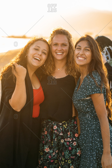 A colorful portrait of three beautiful women hugging on the beach with the sun behind them Vacation concept Vertical image