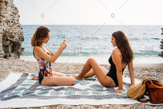 Side view of stylish young women in swimwear relaxing on seashore taking picture by smartphone and looking at each other