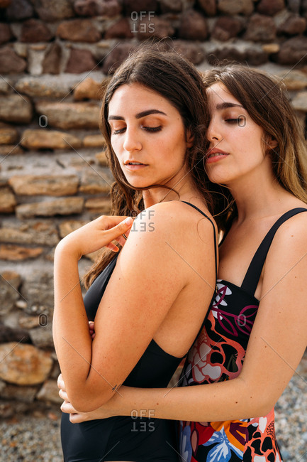 Side view of pretty alternative women in swimsuits standing with closed eyes enjoying embracing by shabby stone construction