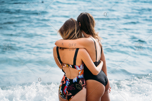Back view of young alternative women in swimsuits standing by sea embracing and contemplating seascape on sunny day