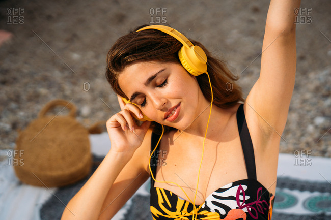 Happy female teenager in colorful swimsuit and yellow headphones enjoying music with closed eyes while relaxing on beach