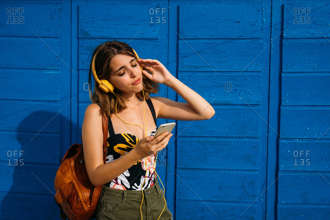 Young positive woman with backpack standing by colorful wooden wall listening to music on the mobile phone smiling with closed eyes