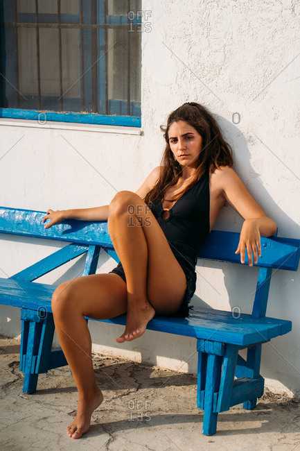 Slim beautiful woman looking at camera sitting on wooden bench by stone building on sunny day
