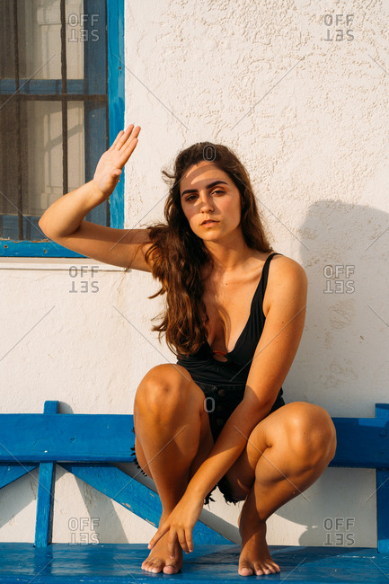 Slim beautiful woman looking at camera squatting on wooden bench by stone building on sunny day