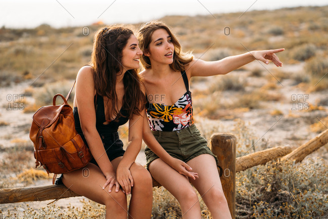 Pretty young women with backpack relaxing on wooden fence chatting pointing with forefinger and looking away on blurred nature background