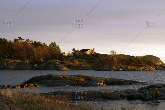 Grey rocks and house at peaceful seaside on chilly misty day with light colorful sky