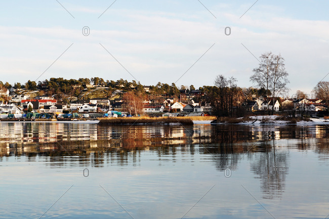 Winter river bank with leafless trees and colorful houses in distance