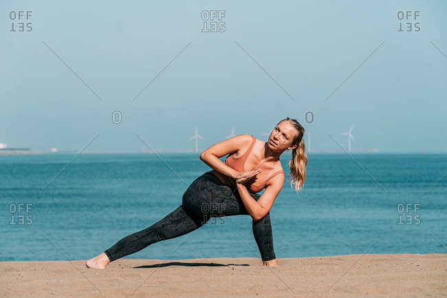 Side view of focused blond woman in sportswear doing asana while standing on seashore in sunlight