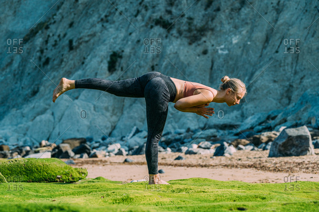 Side view of fit calm woman doing asana with one leg raised back while standing on colorful ground beside cliff