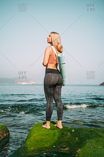 Woman with yoga mat contemplating on green seashore