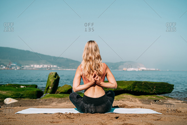 From behind sportive woman practicing yoga asana with hands behind back while sitting on mat at tranquil coast