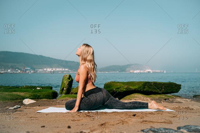 Peaceful woman meditating on scenic seashore