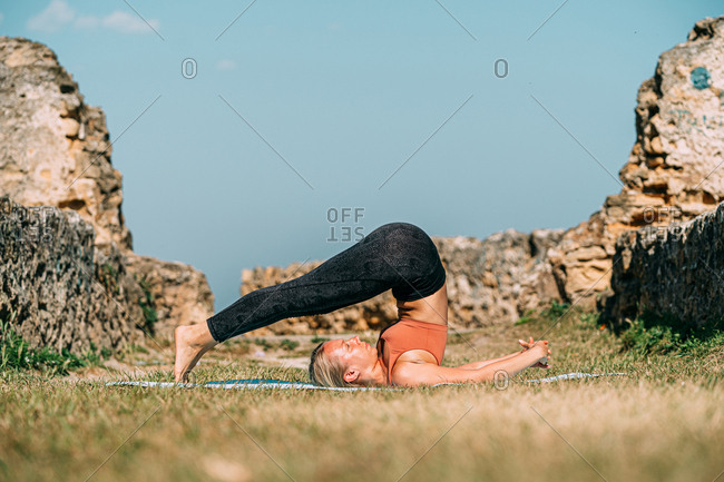 Flexible woman stretching and practicing yoga at sunny countryside