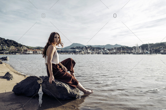 Red haired woman in stylish clothes sitting on big stone and looking along submerging feet in water