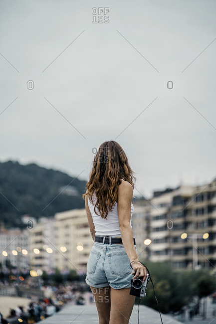 Back view of young active slim woman in shorts with camera in hands looking at evening view of city lights and buildings in street