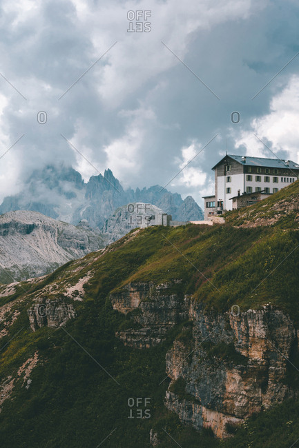 White and gray building on rocky hill with green thick grass against beautiful mist mountains in Dolomites during overcast weather