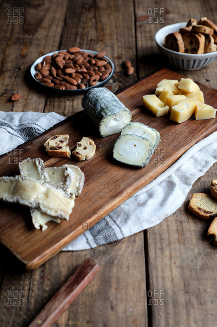 Sweet croutons with raisins and plate with almonds placed on wooden table near board with various cut cheese