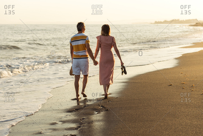 Back view of barefoot man and woman holding hands and carrying shoes while walking on sandy beach towards waving sea on resort