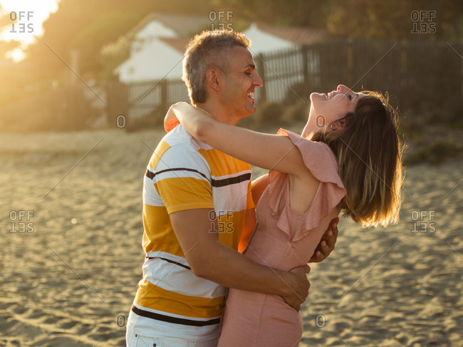 Excited adult man and woman laughing and embracing each other while having fun on sandy shore on resort