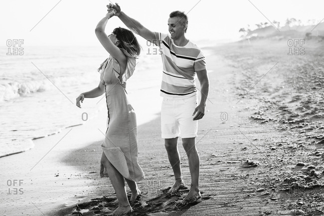 Full body adult man smiling and spinning woman in dance while having fun on sandy beach near sea