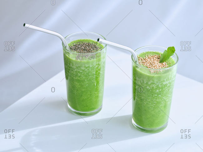 Glasses of green smoothie on white table