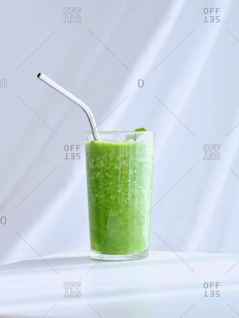 Glass of green smoothie on white table