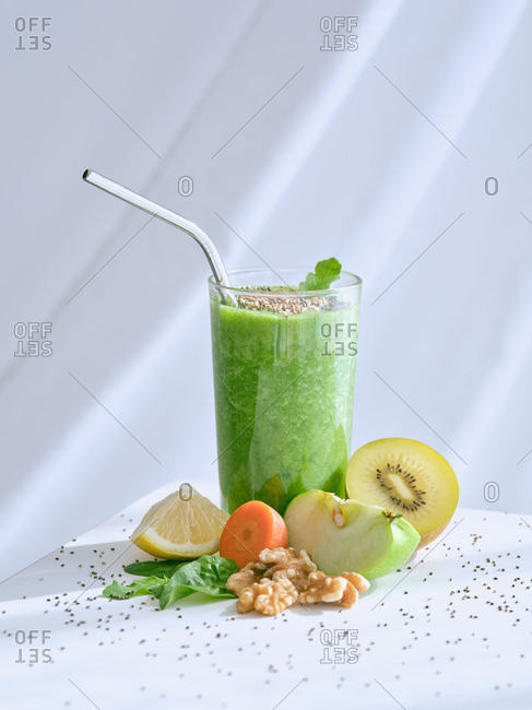 Set of ingredients for healthy smoothie and glass with green drink