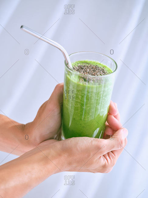 Person holding glass of green smoothie
