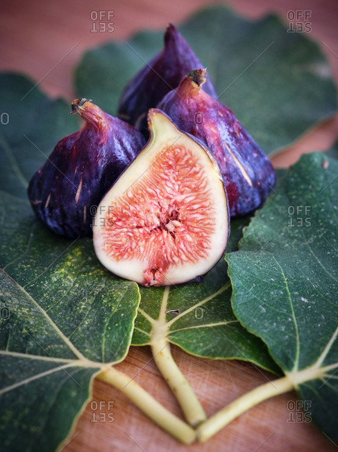 chopped fig and figs over wooden table with green leaves