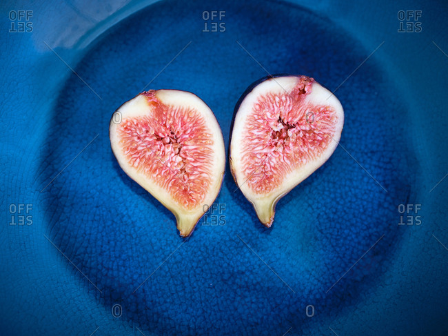 top view of half pieces of fig over blue plate