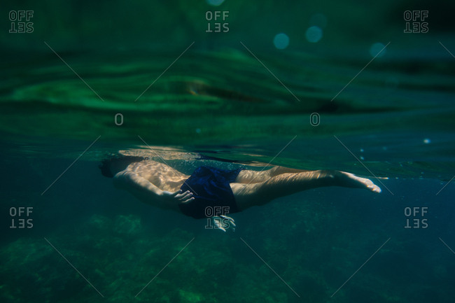Sportive active man in shorts swimming under water of sea while enjoying vacation