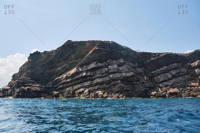 Transparent sea waves against huge cliff