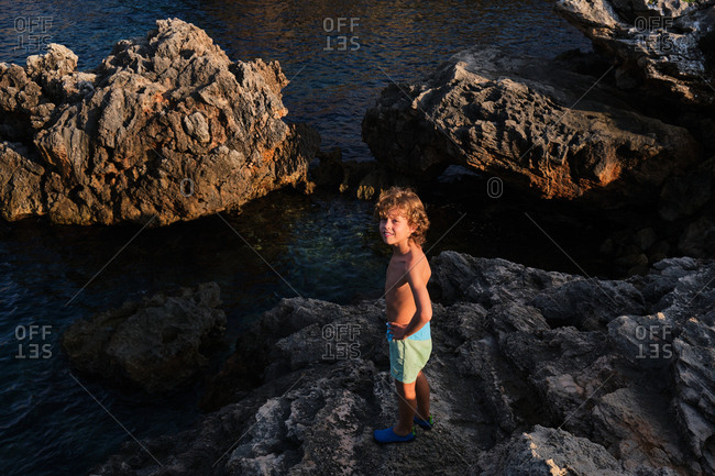 From above of joyful kid standing on cliff above sea water and smiling at camera in sunset light