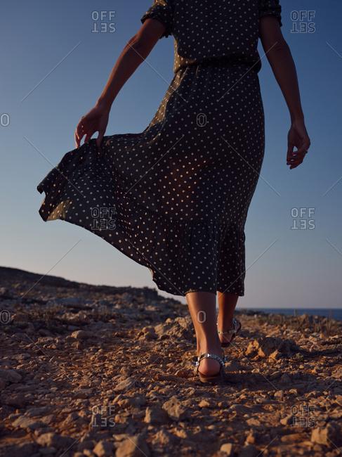 Woman walking on beach while wind waving dress