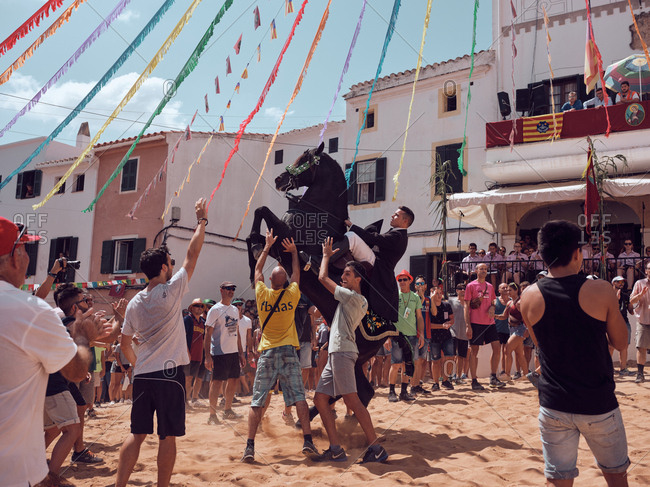 August 25, 2019: Spain, Menorca August 25, 2019: Side view of rider in festive suit sitting on black horse floundering in sandy arena surrounded by surprised joyful people