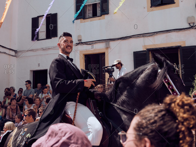 August 25, 2019: Spain, Menorca August 25, 2019: Well-dressed sleigh riders walking on horses along festively decorated streets under gazes of joyful lively people