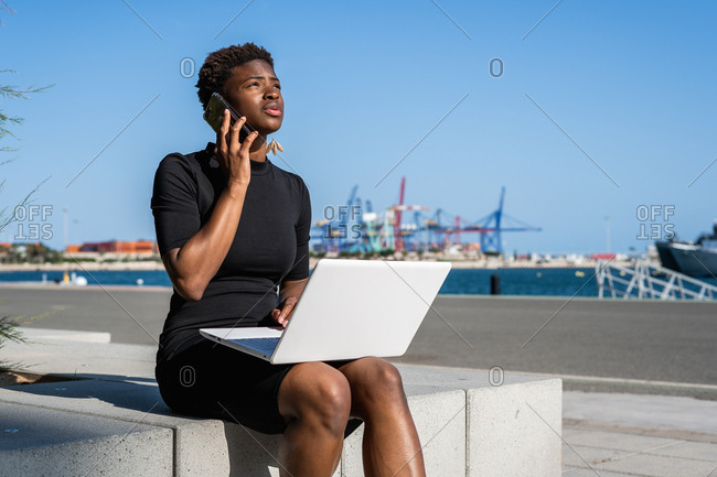 Disappointed African American woman in black dress using laptop and talking on smartphone on street on blurred background