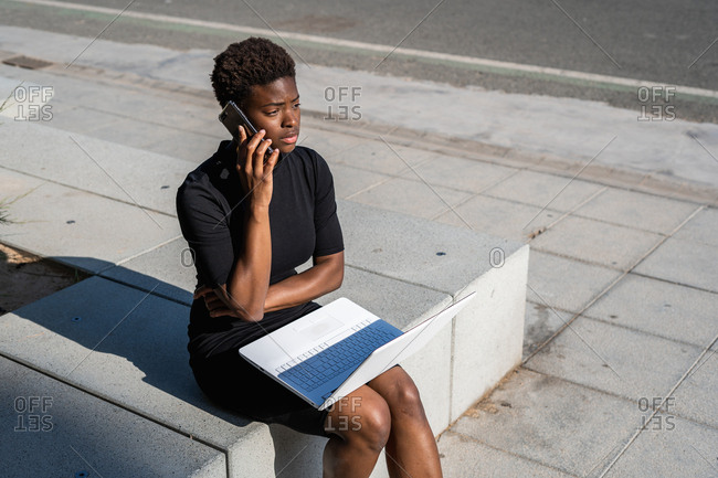 Concentrated African American woman in elegant black dress using laptop and speaking on the mobile phone while sitting on pavement on street