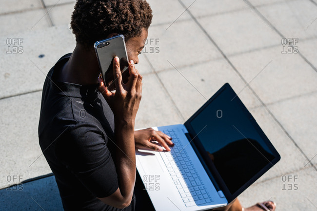 African American woman in elegant black dress using laptop and speaking on the mobile phone while sitting on pavement on street
