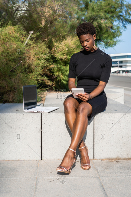 Concentrated African American woman in elegant black dress using mobile phone near a laptop while relaxing on pavement on street