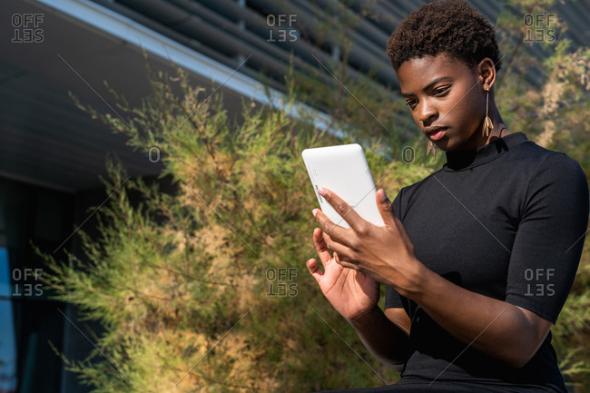 African woman in elegant black dress using mobile phone while sitting on pavement on street