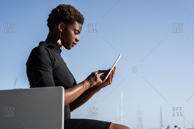 Side view of concentrated African American woman in elegant black dress using mobile phone while sitting on pavement on street