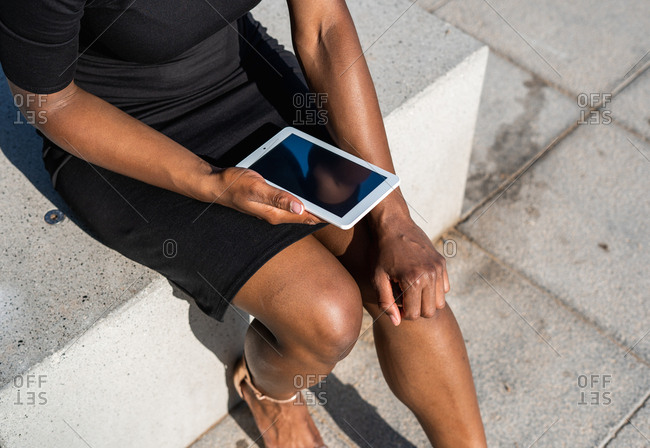 Cropped unrecognizable black woman in elegant black dress using mobile phone while sitting on pavement on street