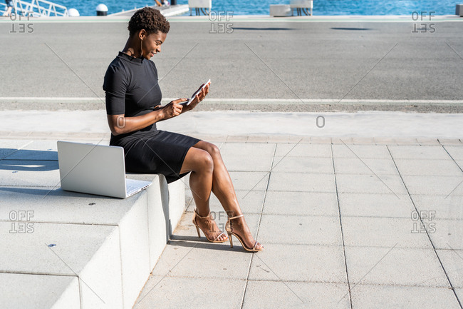 Side view of concentrated African American woman in elegant black dress using mobile phone near computer while sitting on pavement on street