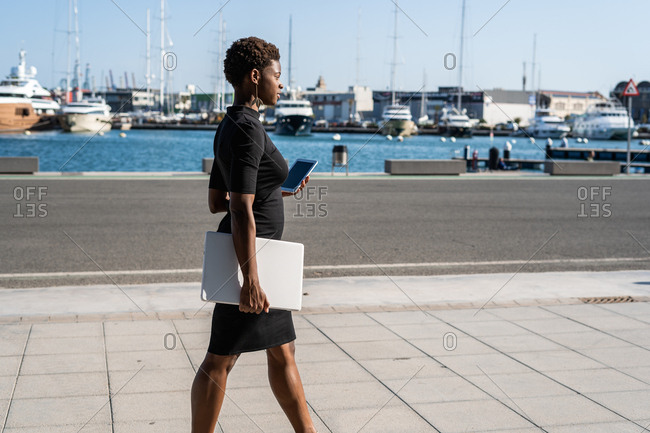 Side view of African American woman in elegant black dress holding laptop and using a mobile phone while walking on pavement on the street