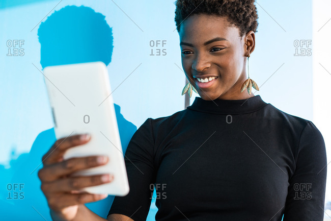 Cool African American smart woman shooting selfie on blue background
