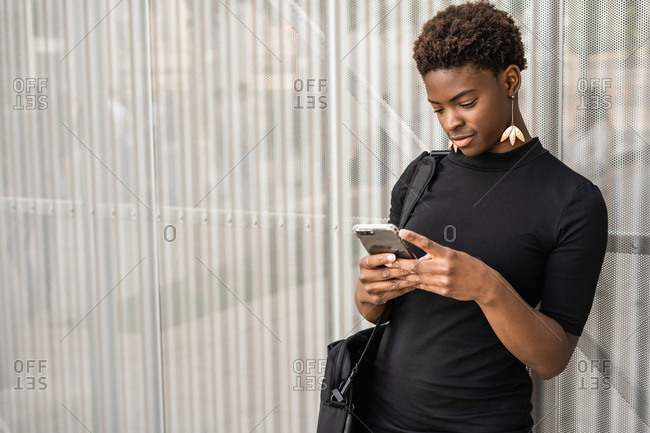 Focused stylish African American woman in black dress messaging smartphone while standing on metal background